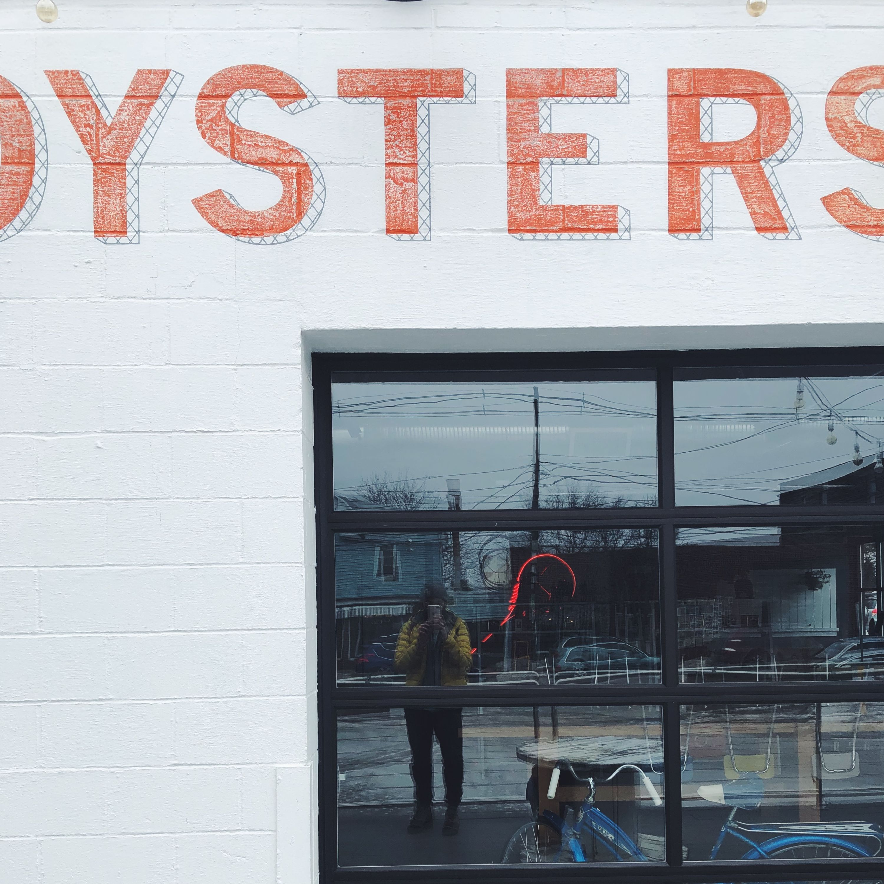 "A building with some hand lettered typography: ""oysters""."