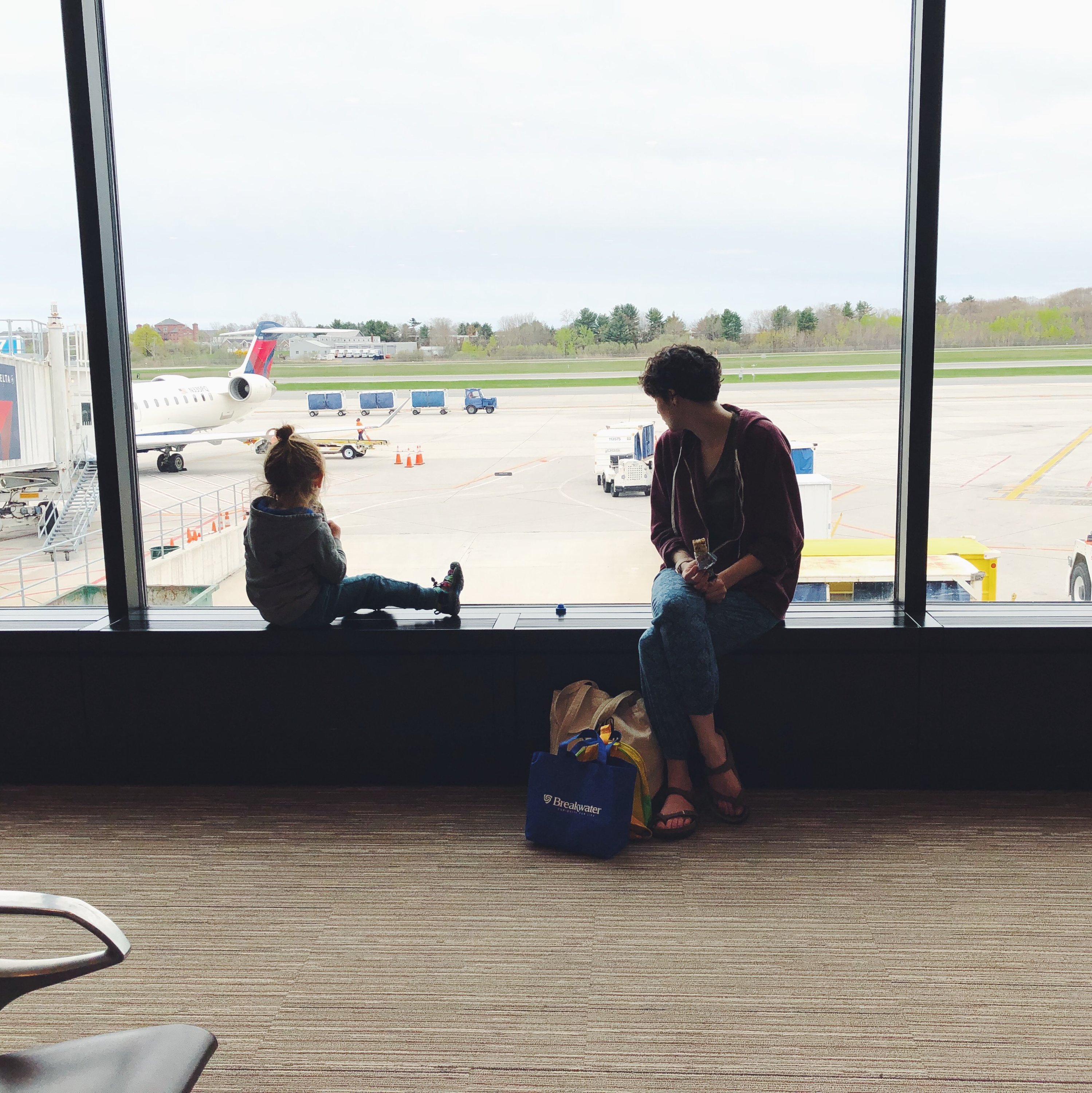 Kid and mom looking out an airport window at planes and equipment.