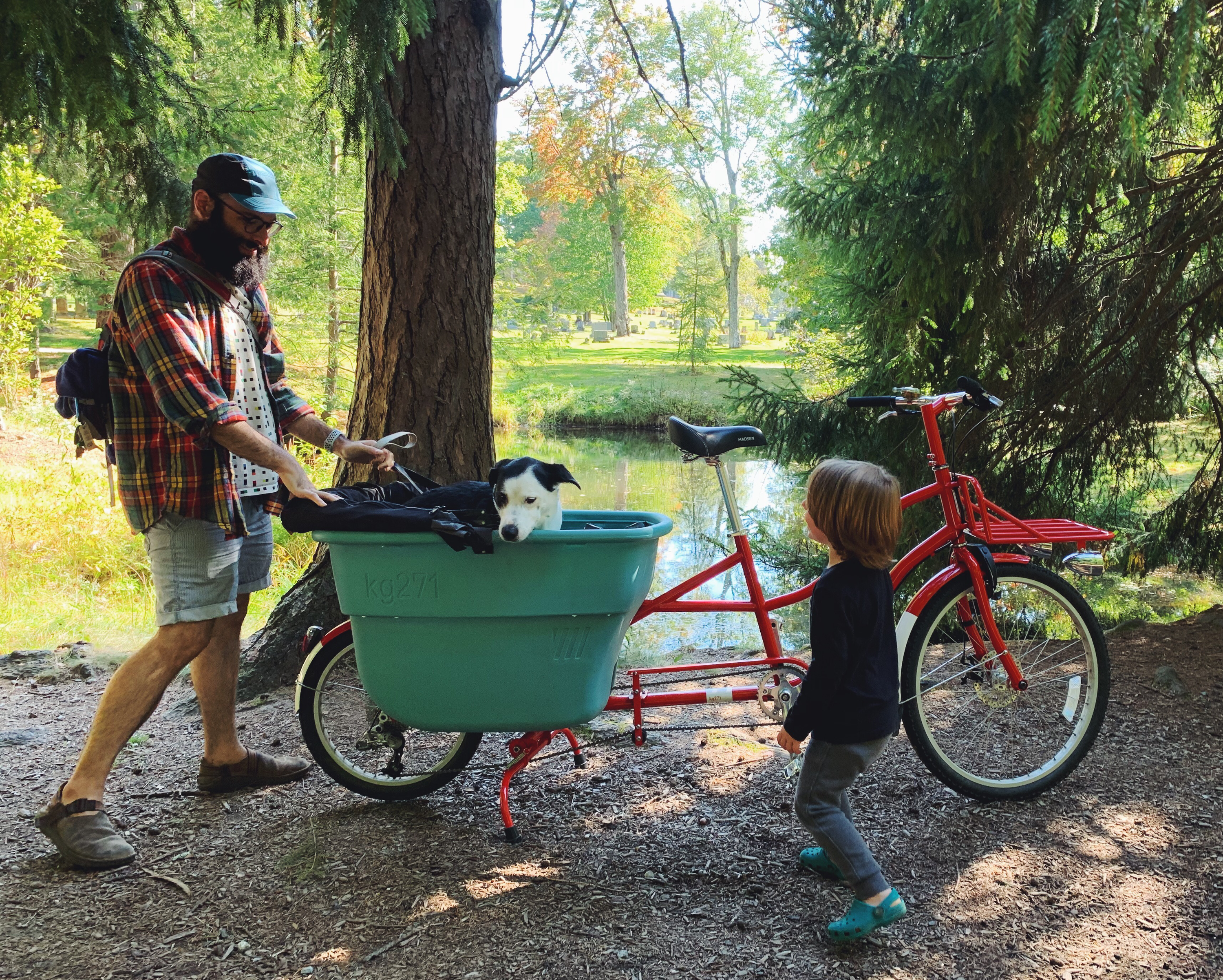Bearded man and red headed kid stand around a cargo bike. A dog is in the bike. The dog is not happy.