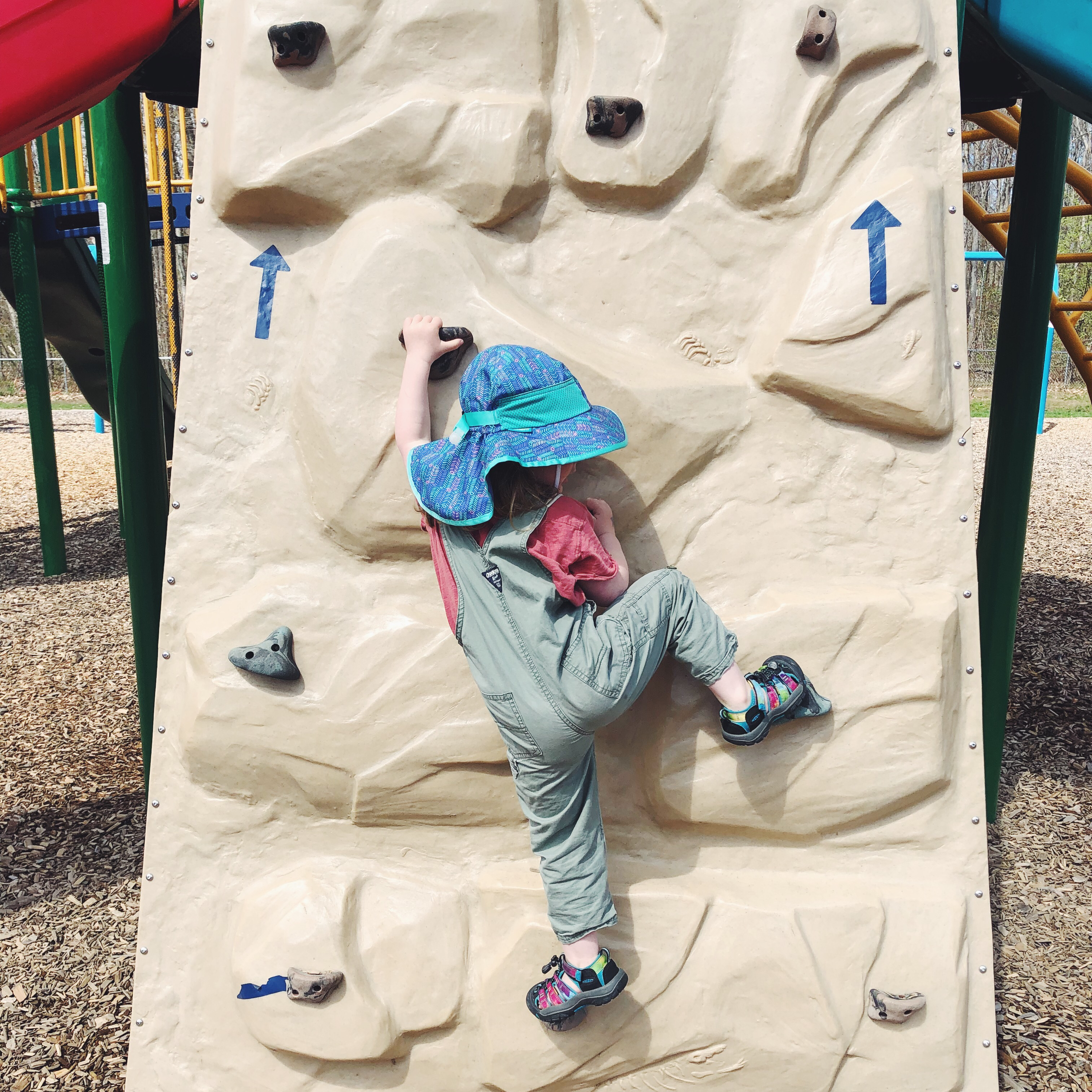 A child in a large, purple, floppy sun hat climbs a wall at a playground.