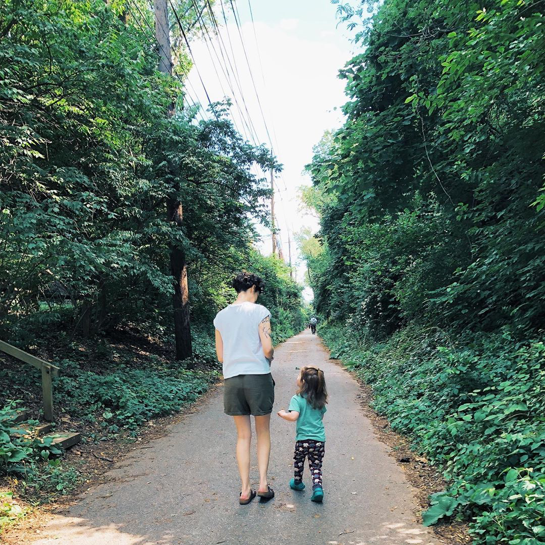 Mom and son walk down wooded path.