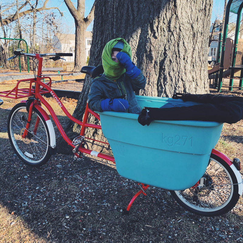 Very bundled kid sitting in a bucket bike at a playground.