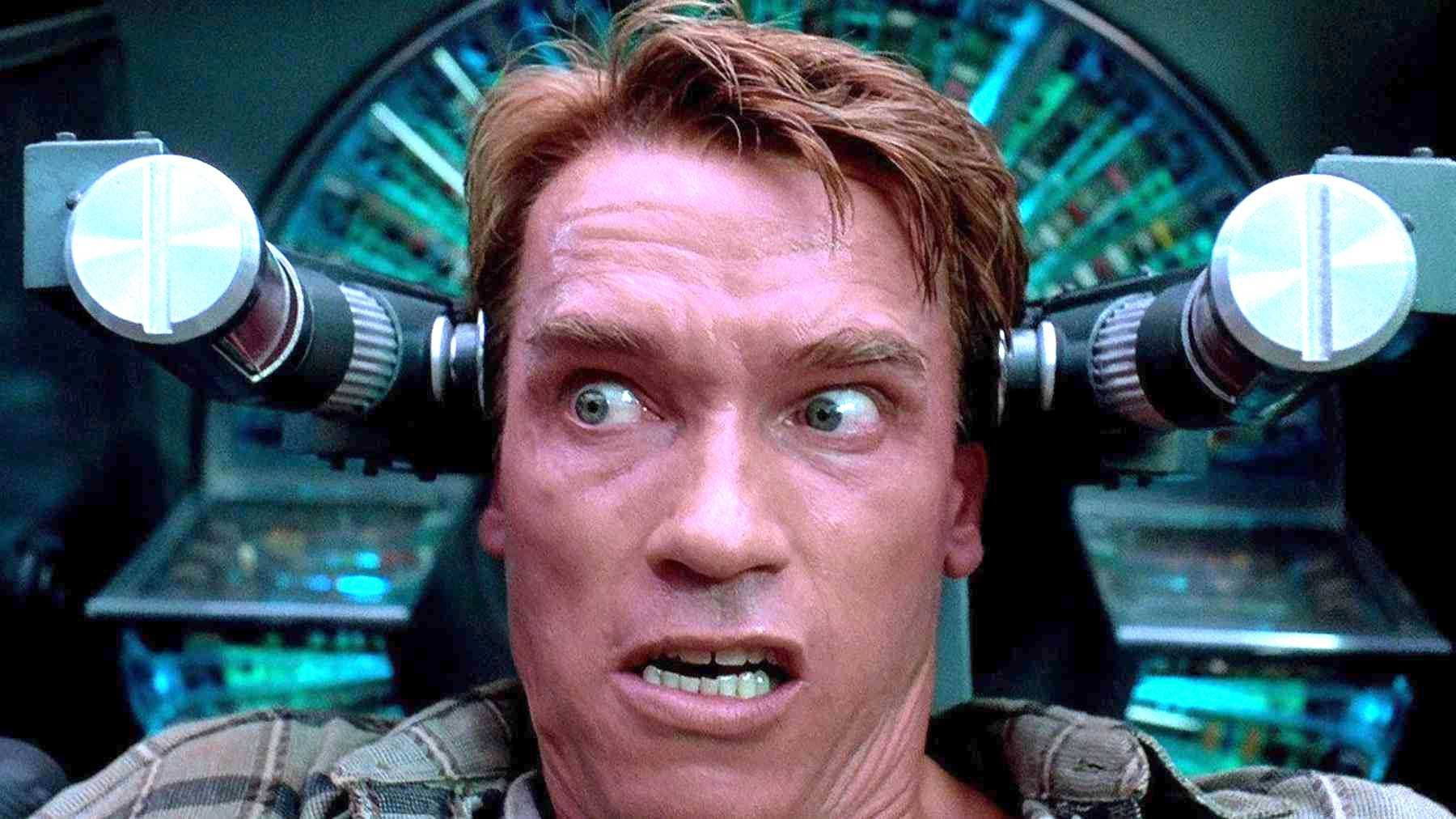 Arnold sitting in the memory implantation chair from Total Recall