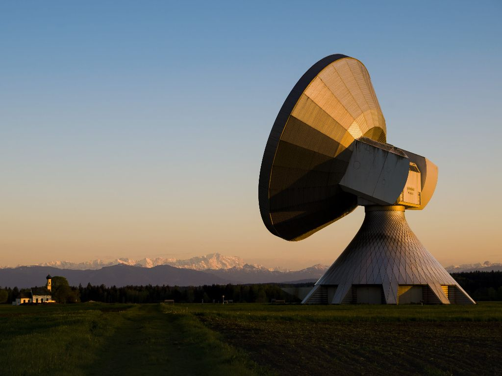 Radar installation at sunset with mountains in the distance