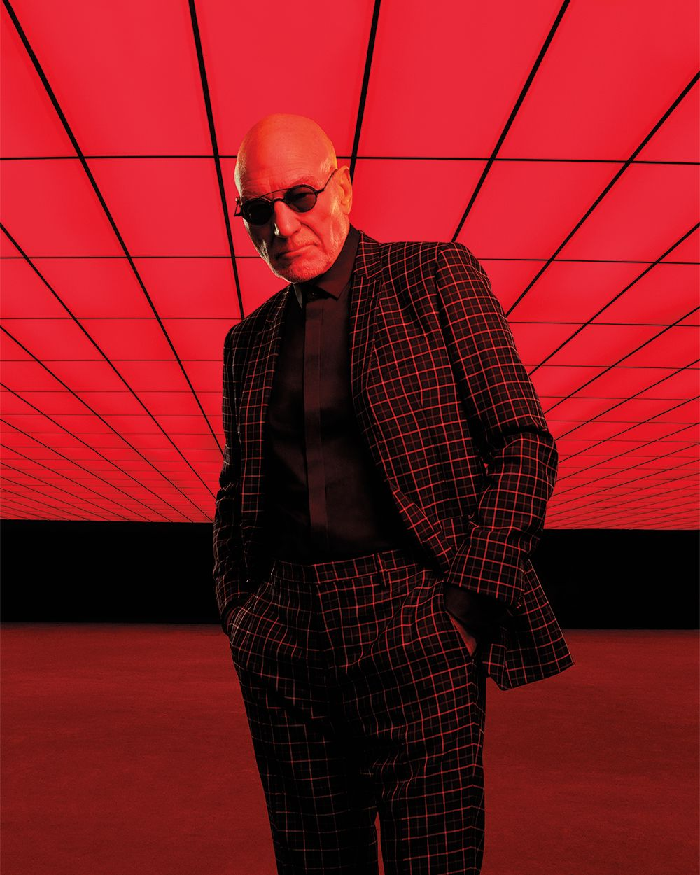 Patrick Stewart in a black suit with a red windowpane check. He is wearing sunglasses.